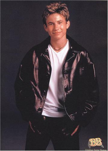 The 90s wallpaper with a business suit and a well dressed person titled Jonathan Taylor Thomas