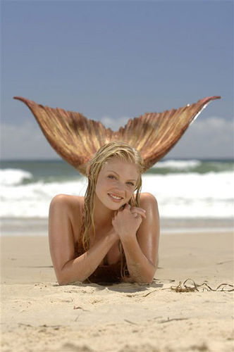 Rikki laying on the strand as a mermaid