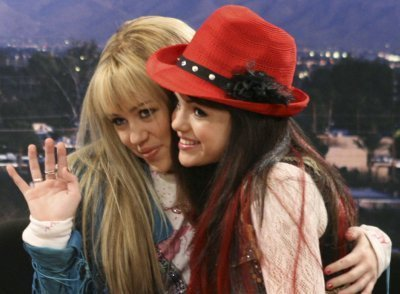 Miley Cyrus vs. Selena Gomez 壁纸 probably with a fedora called hannah and micayla