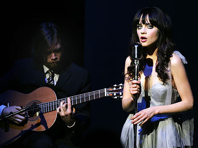 What is the name of the group Zooey sings with?