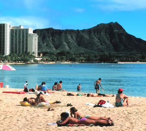 What is the name of the crater (pictured in the background) that overlooks Waikiki beach?
