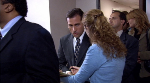 When Pam approaches Michael in the line for pretzels, what is the first thing he says to her?