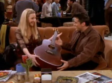 When Phoebe gives Joey guitarra lessons, which of these is not a hand position she teaches him?