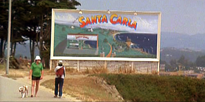 What is written on the back of the Santa Carla sign?